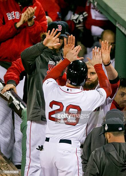 Red Sox player Daniel Nava gets high fives from Jonny Gomes after scoring the Red Sox's eighth and final run in the eight inning of Game One of the...