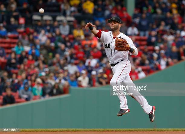 Red Sox player Dustin Pedroia throws to first after catching Braves player Nick Markakis grounded out to second during the fourth inning of a game...