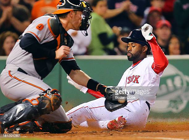 Red Sox player Jackie Bradley slides safely into home beating the tag by Orioles' catcher Matt Wieters in the second inning on an RBI by Pedroia The...