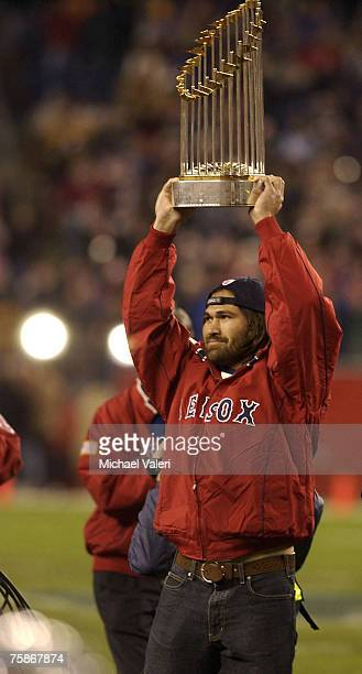 Red Sox player Johnny Damon holds the Red Sox World Series trophy high for the Patriots fans to see prior to a game between the Buffalo Bills and the...
