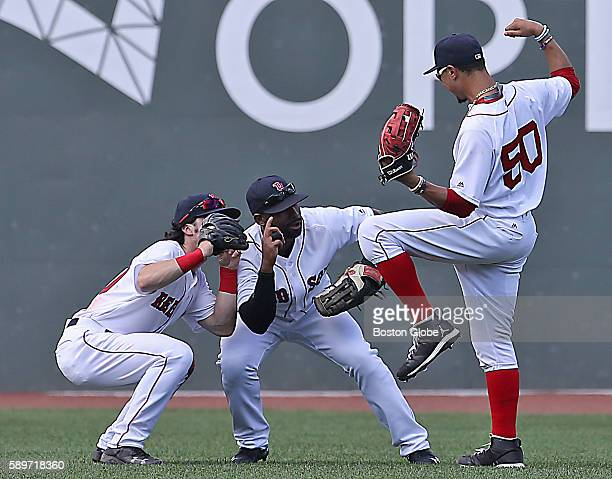 Red Sox player outfielders Andrew Beninetendi and Jackie Bradley Jr pretend to take a photo of Mookie Betts who hit three home runs in the game as...