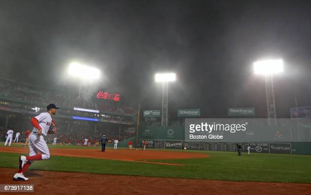 Red Sox right fielder Mookie Betts heads for his defensive position as fog envelops Fenway Park The Boston Red Sox host the New York Yankees in a...
