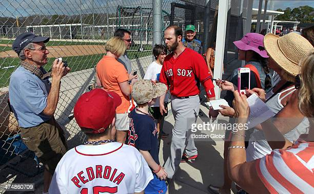 Red Sox second baseman Dustin Pedroia signed a quick autograph for a young fan as he moved from one field to another during drills during Boston Red...
