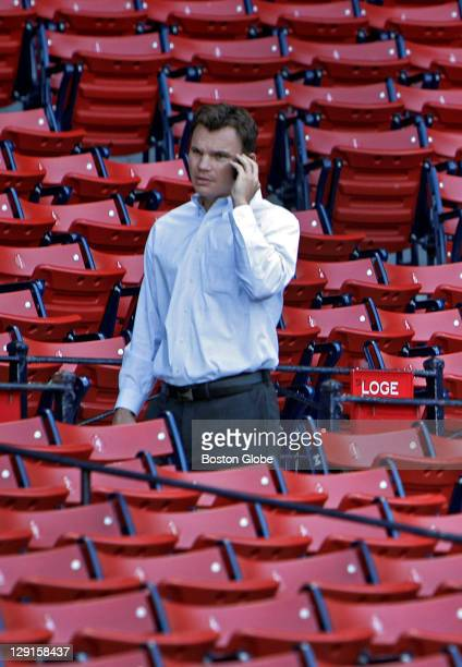 Red Sox senior vice president/assistant general manager Ben Cherington talks on his cell phone as he walks through the empty stands at Fenway Park...