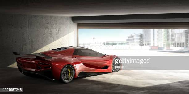 red sports car in open door garage on bright day - prestige car stock pictures, royalty-free photos & images
