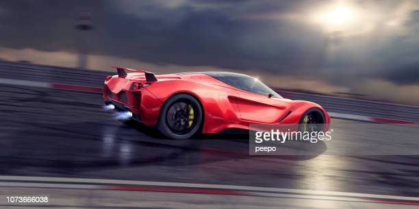 red sports car moving fast on racetrack with exhaust flames - muscle car stock photos and pictures