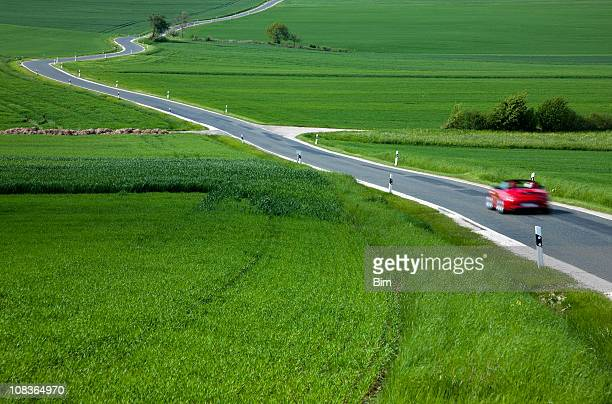 Red Sports Car Speeding on Rural Winding Road in Spring