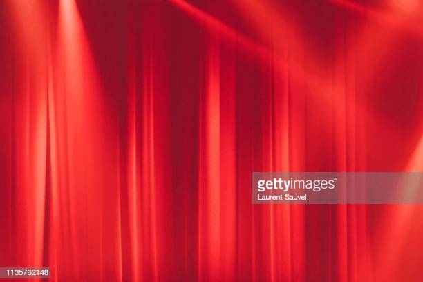 red stage curtain in the spotlights with light rays - ドレープ ストックフォトと画像