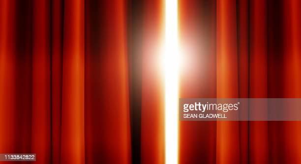 red stage curtains with light shining through - film oder fernsehvorführung stock-fotos und bilder