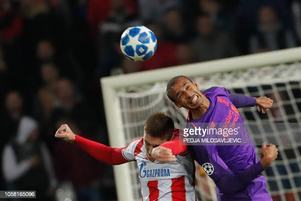 Red Star Belgrade's Serbian forward Milan Pavkov and Liverpool's Cameroonian defender Joel Matip jump for the ball during the UEFA Champions League...