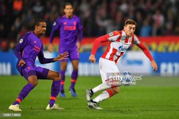 Red Star Belgrade's Serbian forward Milan Pavkov vies for the ball with Liverpool's Cameroonian defender Joel Matip during the UEFA Champions League...
