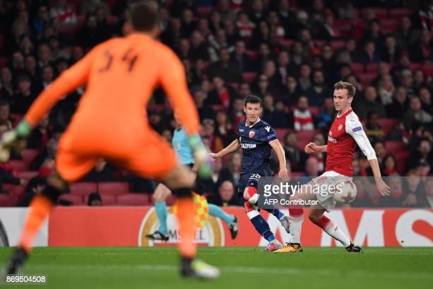 Red Star Belgrade's Serbian midfielder Slavoljub Srnic crosses the ball past Arsenal's English defender Rob Holding during the UEFA Europa League...