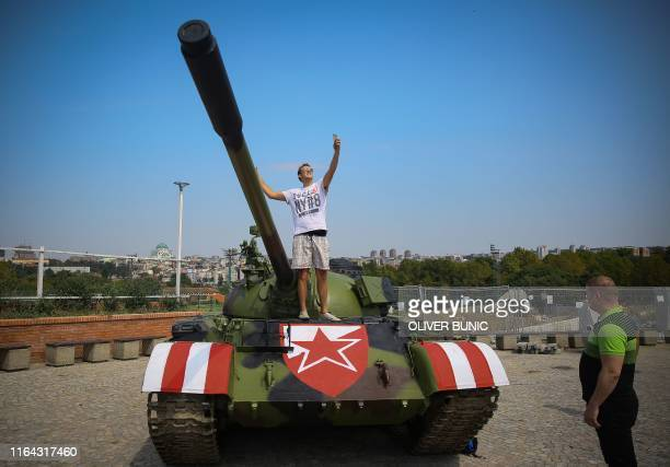 Red Star fan takes a selfie as he stands on a former Yugoslav army T55 tank parked at the northern grandstand of the Rajko Mitic stadium in Belgrade...