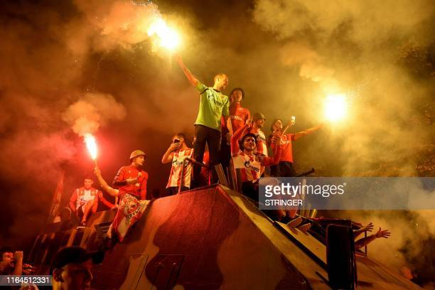 TOPSHOT Red Star fans celebrate their Champions League qualification with flares on top of an armoured vehicle parked at the northern grandstand of...