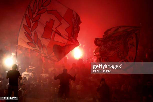 Red Star supporters wave flags and light flares during the Serbian Cup semi-final football match between FK Partizan Belgrade and Red Star Belgrade...