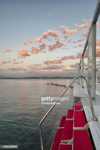 red steps descending to the aegean sea in cesme. - emreturanphoto stock pictures, royalty-free photos & images
