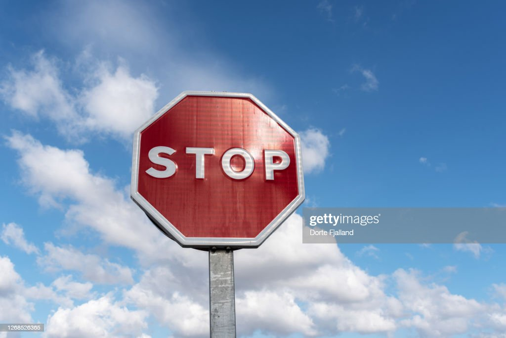 Red stop traffic sign against a blue and white sky : Foto de stock
