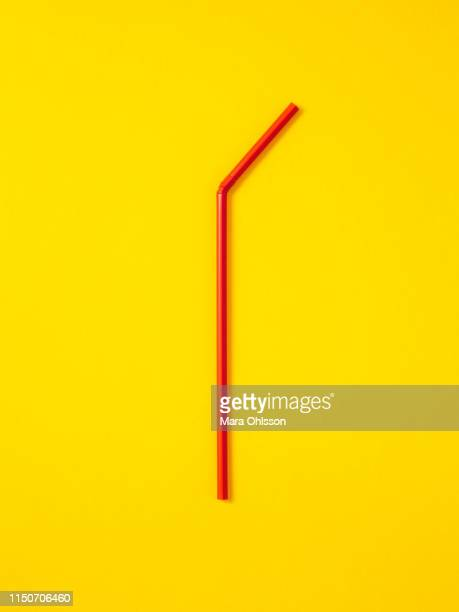 red straw laid vertically on yellow background - drinking straw stock pictures, royalty-free photos & images