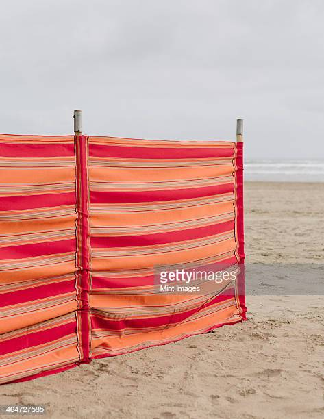 a red striped windbreak on cannon beach on the oregon coast. - manzanita stock pictures, royalty-free photos & images