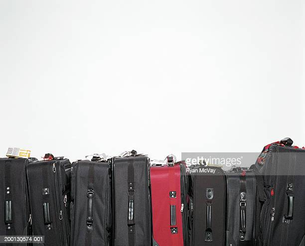 Red suitcase amongst row of black suitcases