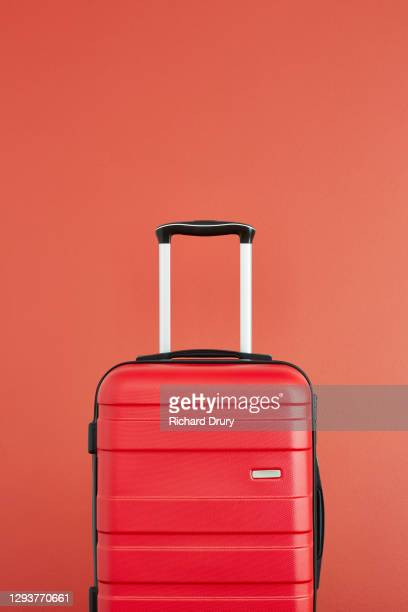 a red suitcase on a red background - bright colour stock pictures, royalty-free photos & images