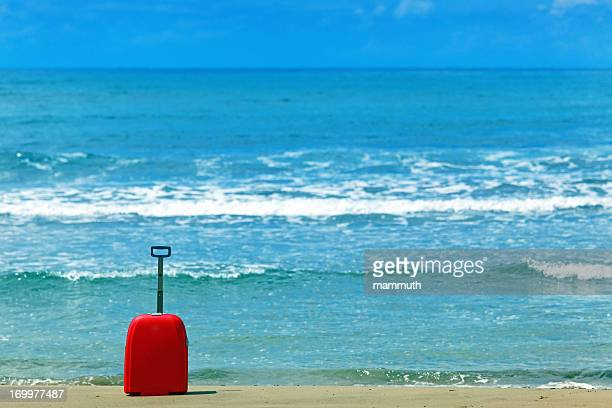 red suitcase on the beach