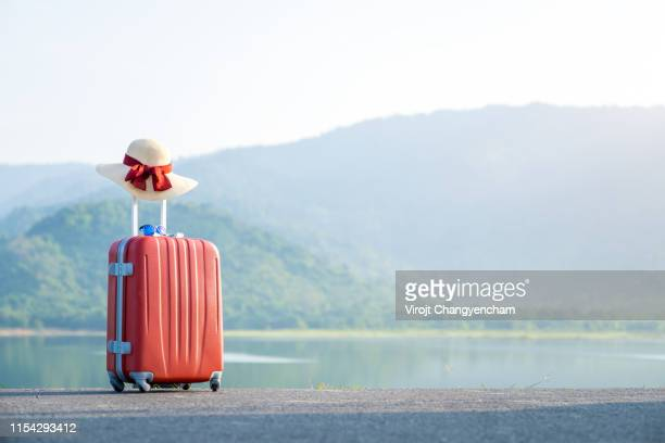 red suitcase with nature background, vacation and traveling concept. - luggage stock pictures, royalty-free photos & images