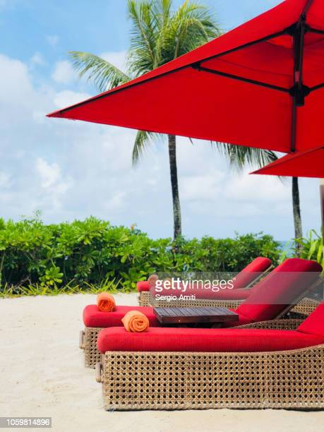 Red sun lounges and red beach umbrellas