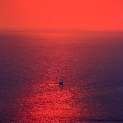 Red sunset over Aegean Sea and lone sailboat, Greece - gettyimageskorea