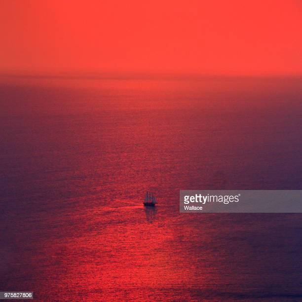 Red sunset over Aegean Sea and lone sailboat, Greece