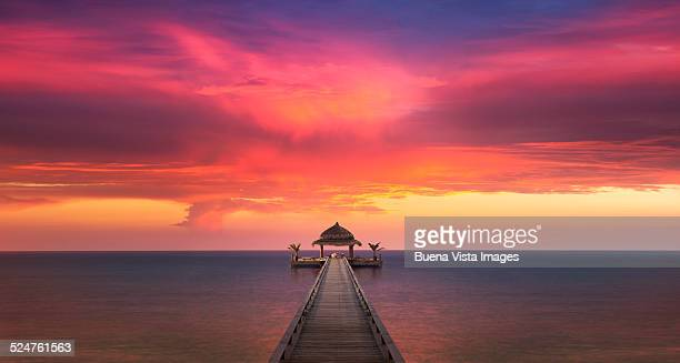 red sunset over dock on ocean