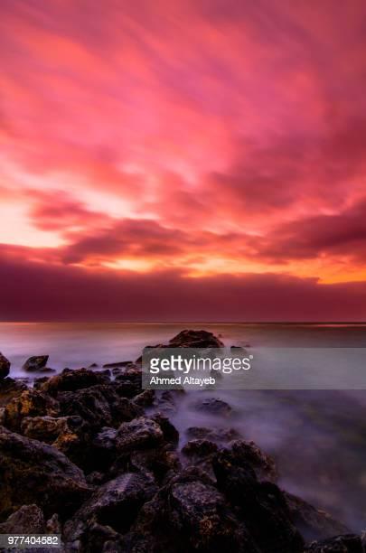 red sunset over rocky coast, zallaq, bahrain - bahrain foto e immagini stock