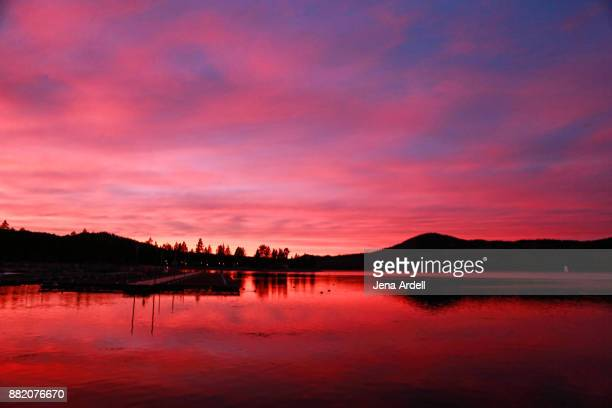 red sunset over water - big bear lake stock photos and pictures