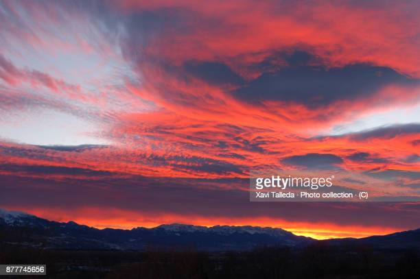 A red sunset with ring shaped clouds over Cadí mountain range