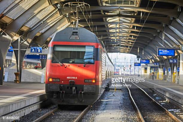 Red Swiss train approaching platform of the modern Zurich Central Station