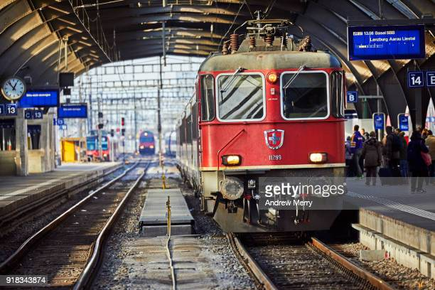 Red Swiss train on platform at Zurich Central Station, with coat of arms of Switzerland on front of train