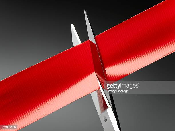 red tape being cut by scissors, close-up - bureaucracy stock pictures, royalty-free photos & images