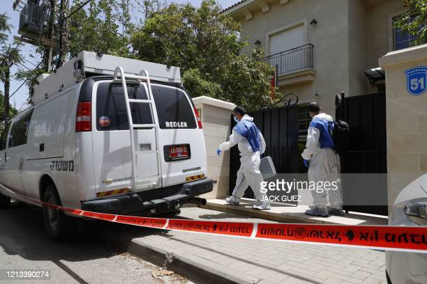 Red tape blocks the entrance to the residence of Israel's Chinese ambassador on the outskirts of Tel Aviv, as forensic experts walk out, after he was...