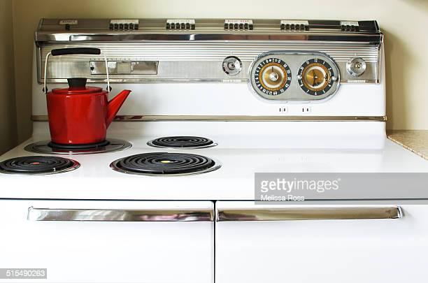 Red tea kettle on a vintage stove or range