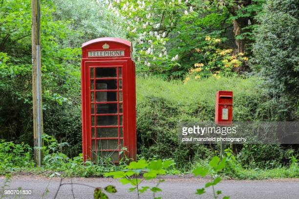 Red telephone and postal box in countryside