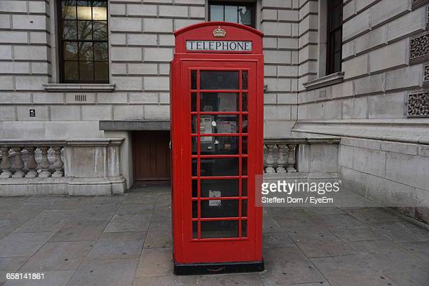 Red Telephone Booth Against Building