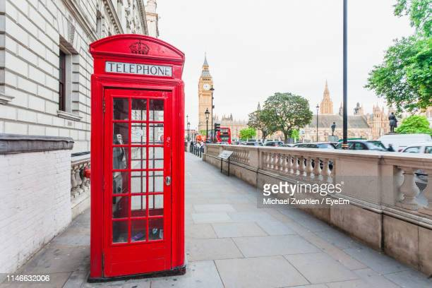 red telephone booth on sidewalk in city - red telephone box stock pictures, royalty-free photos & images
