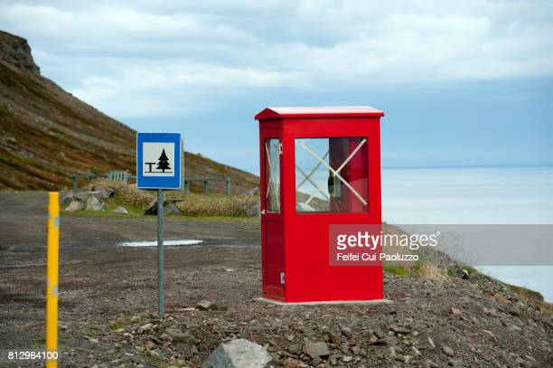 Red telephone box at rest area of Eydafjordur, in the eastfjord of Iceland