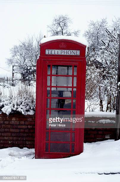 red telephone box covered in snow by garden wall, winter - red telephone box stock pictures, royalty-free photos & images