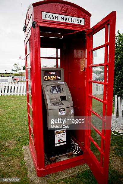 Red Telephone Box housing an ATM cash machine on lawn beside the Assembly Area at Goodwood on September 10 2016 in Chichester England