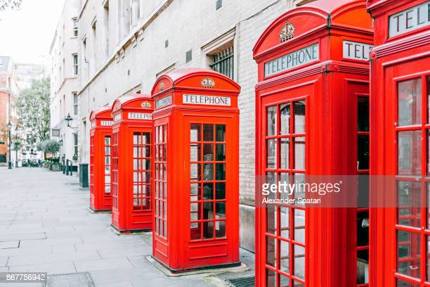 Red telephone boxes standing in a row on a street in London, The UK