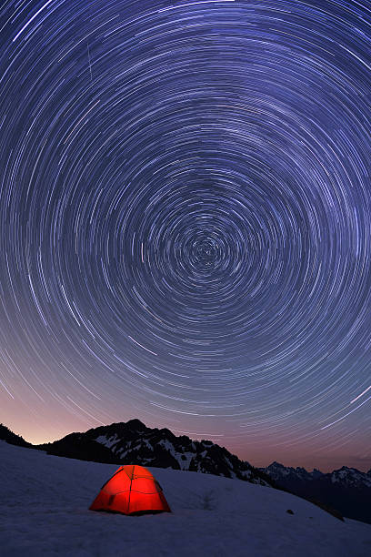 Red tent and Star Trails on snow mountain