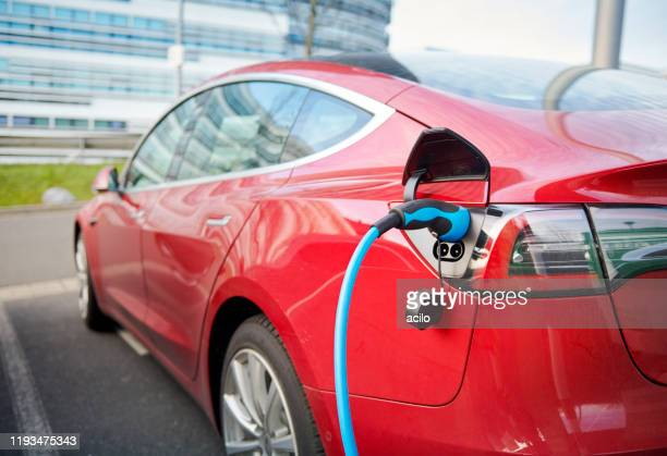 red tesla model s electric car connected to a recharging station - tesla motors stock pictures, royalty-free photos & images