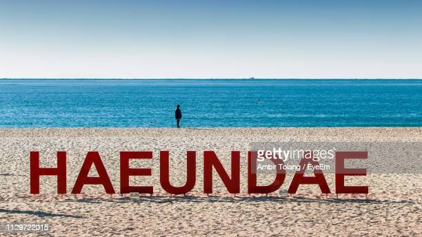 red text at beach with child in background - busan stock pictures, royalty-free photos & images