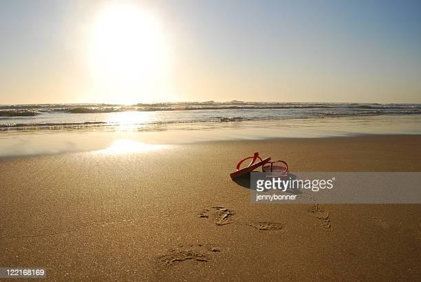 Red Thongs Flip Flops on Beach Coastline at Sunset